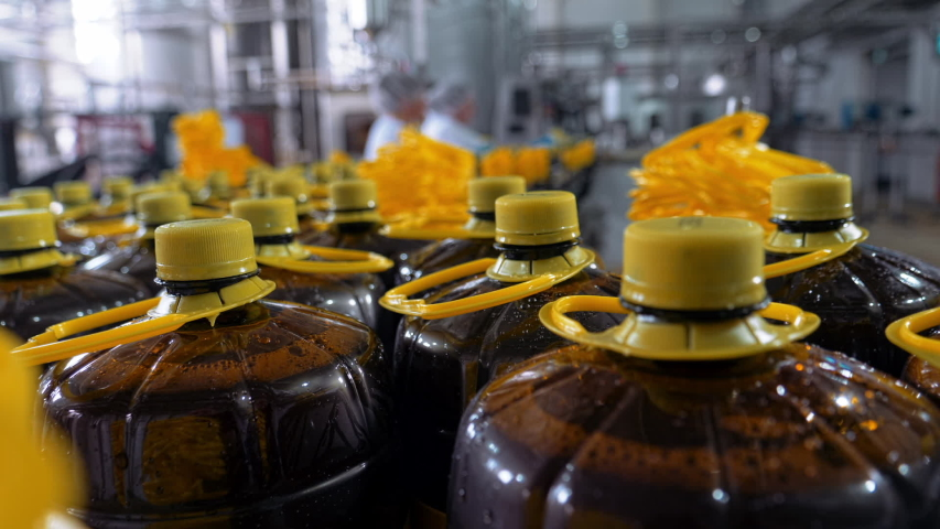 Plastic bottle yellow caps close up, soft drink factory line, beverage on automated industrial line, conveyor, modern plant, slow motion | Shutterstock HD Video #1055581682