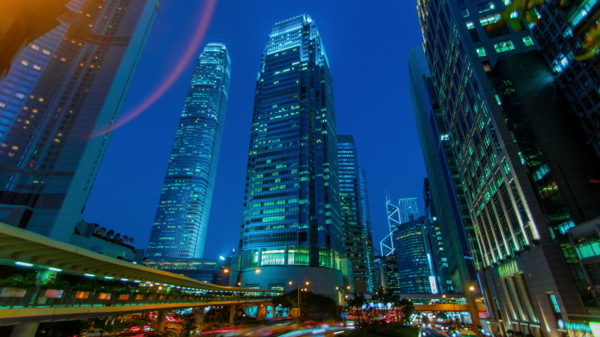 Time-lapse of a futuristic Hong Kong street in the Central business district, depicting some of the city's landmarks. From sunset to night, with bright neon lights against blue hour sky. | Shutterstock HD Video #1055583959