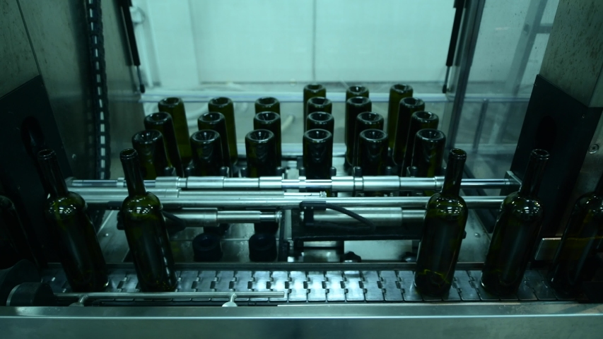 Conveyor with wine bottles at wine factory white wine production, bottle washing | Shutterstock HD Video #1055588549