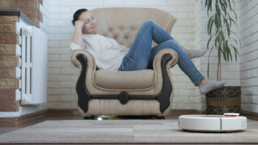 Hoover help. A good looking woman dream in the armchair by the working smart hoover. | Shutterstock HD Video #1055590400