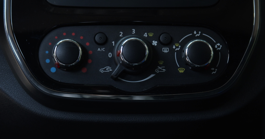 hand raises the air conditioning capacity on the dash and control panel of a car | Shutterstock HD Video #1055597039
