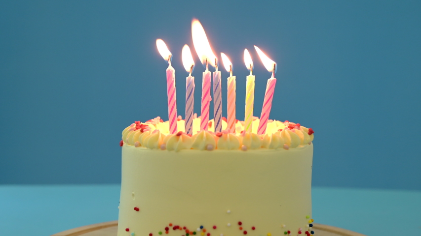 4K Burning candles in birthday cake.  Colorful candles flame in homemade cake on blue background.Sweet dessert for birthday party. Birthday candles for home party Royalty-Free Stock Footage #1055602613