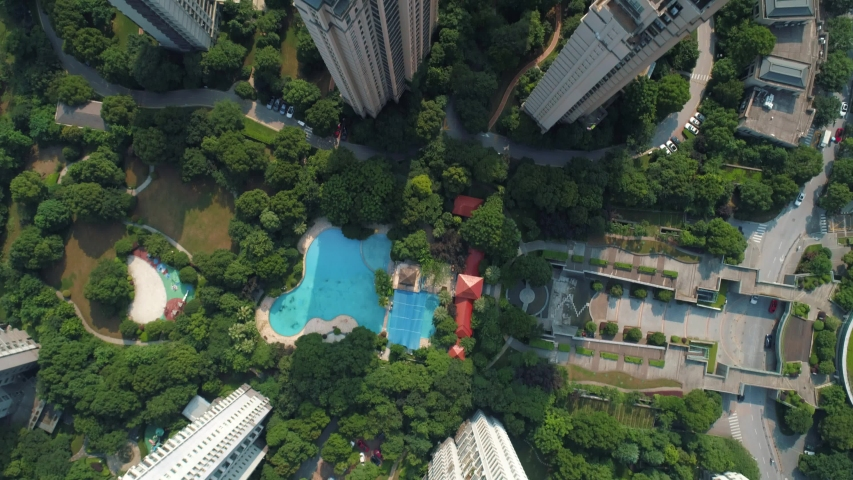 Aerial drone shot over residential apartment buildings on sunny day. Aerial shot over community apartment complex in China. | Shutterstock HD Video #1055607443