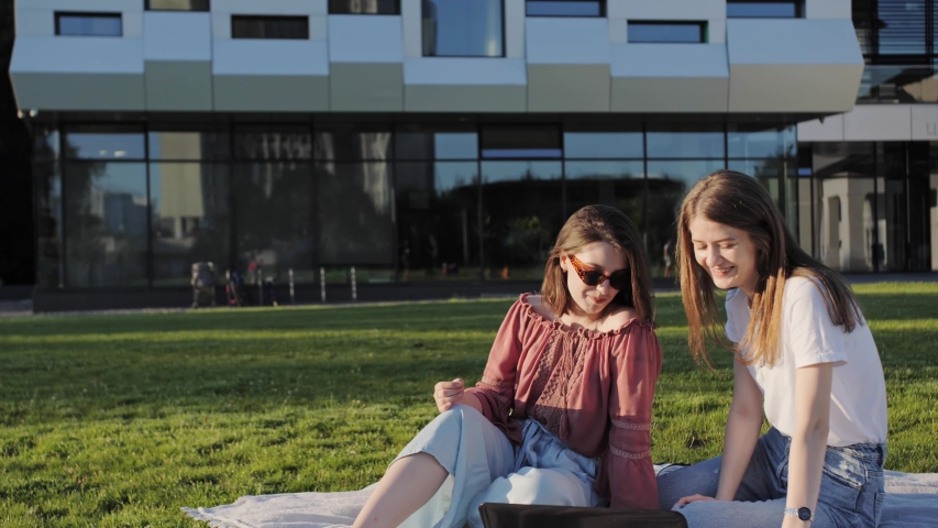 Two girlfriends sitting in the park with a laptop and having fun. Viewing a webinar on entering college | Shutterstock HD Video #1055611340