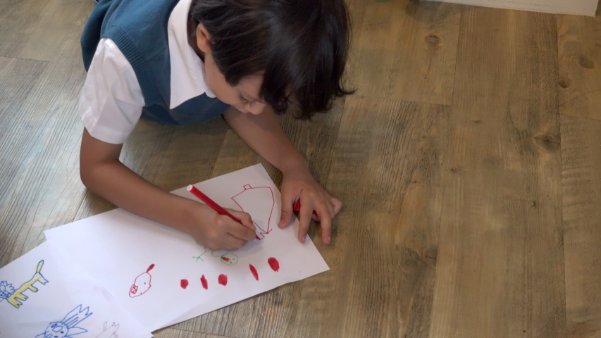 Top view of Happy Asian kindergarten kid boy painting or drawing picture color on paper in the room, Happy childhood education and back to school concept | Shutterstock HD Video #1055616263