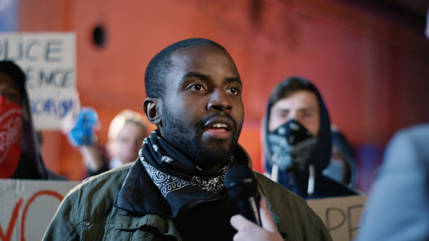 Caucasian female correspondent interviewing aggressive African American man protester at street at night while protesting for human rights and against police violence. Interview of male rebel for news
