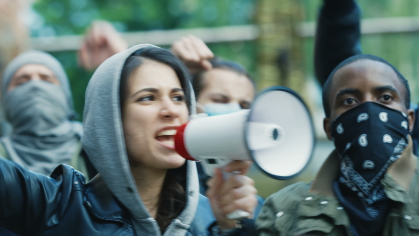 Caucasian young woman leader screaming mottos in megaphone at street in crowd and smoke at protest against racism in USA. Active mixed-races protesters shouting demands. Female leading at rebellion.