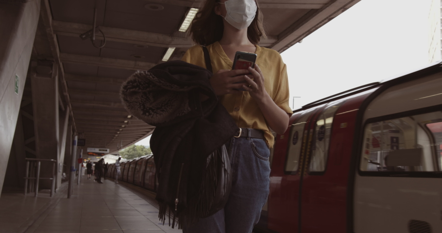 Young adult woman wearing protective medical face mask standing on underground train platform waiting and using mobile smart phone during coronavirus pandemic | Shutterstock HD Video #1055621729