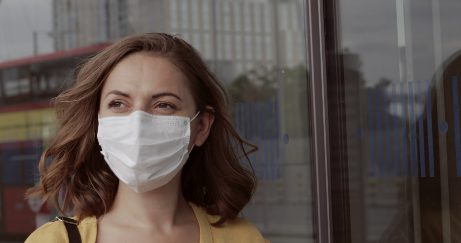 Pretty female in airport bus terminal wearing protective face mask waiting for at bus during covid19 pandemic | Shutterstock HD Video #1055621744
