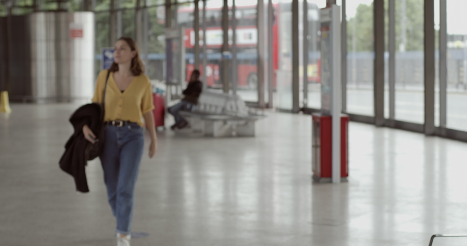 Pretty female sitting in airport terminal using smart phone and waiting for flight information | Shutterstock HD Video #1055621747