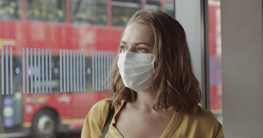 Pretty female in airport bus terminal wearing protective face mask using smart phone during covid19 pandemic | Shutterstock HD Video #1055621750