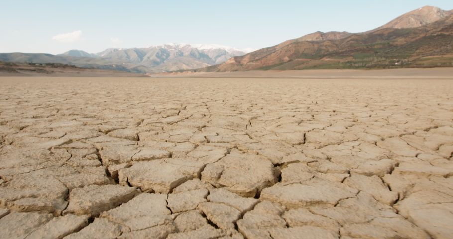 Dynamic shot of cracked soil ground of dried lake or river in mountains. Land destroyed by erosion and global warming - ecological issues concept 4k footage Royalty-Free Stock Footage #1055626388