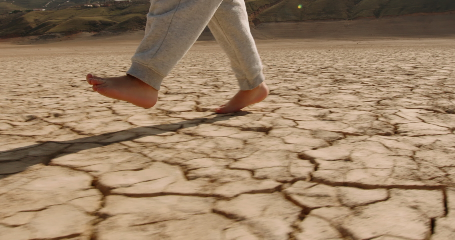 Close up shot of legs of baby boy running on cracked ground, destroyed by erosion, desertification and global warming - environmental issues, save our planet 4k footage Royalty-Free Stock Footage #1055626394