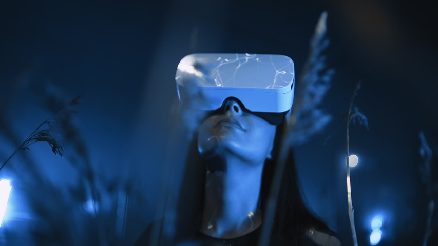 girl uses virtual or augmented reality glasses in magic atmosphere of blue neon rays, female VR headset user on digital interactive art performance, entertainment of future Royalty-Free Stock Footage #1055632004