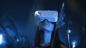 girl uses virtual or augmented reality glasses in magic atmosphere of blue neon rays, female VR headset user on digital interactive art performance, entertainment of future