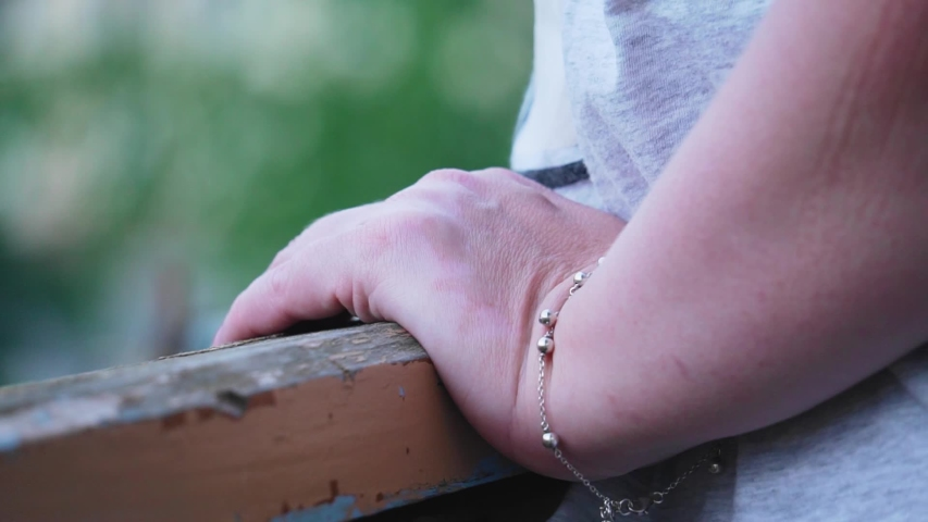 Close-up of a woman's hand on a wooden balcony railing. The girl is resting standing on the balcony | Shutterstock HD Video #1055633843