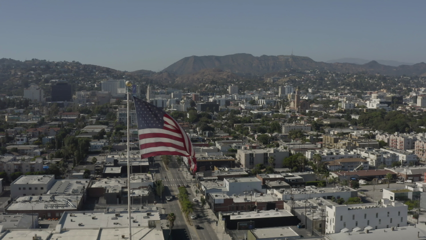 Aerial, panoramic footage of an american flag with Los Angeles and Hollywood in the background | Shutterstock HD Video #1055634002