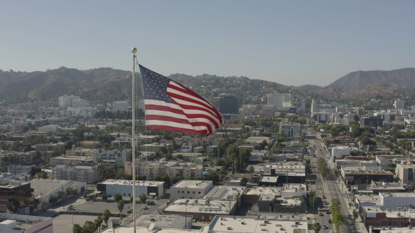 Aerial, reversed footage of an american flag flapping in the wind with Hollywood as a background | Shutterstock HD Video #1055634116