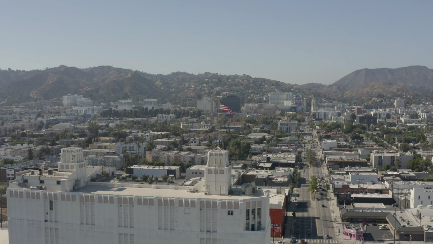 Aerial, tracking shot of an american flag with Hollywood in the background | Shutterstock HD Video #1055634176