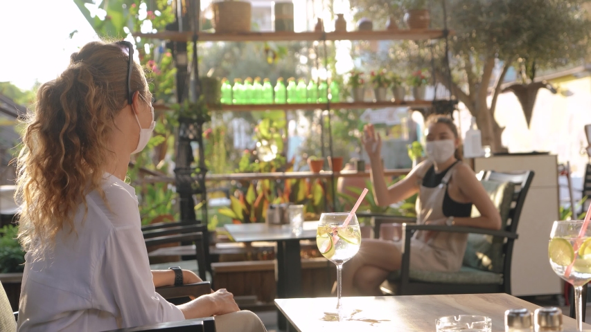 Friends met in a cafe and observe measures of social distance. Two girls communicate at a safe distance. 4K. Royalty-Free Stock Footage #1055634368