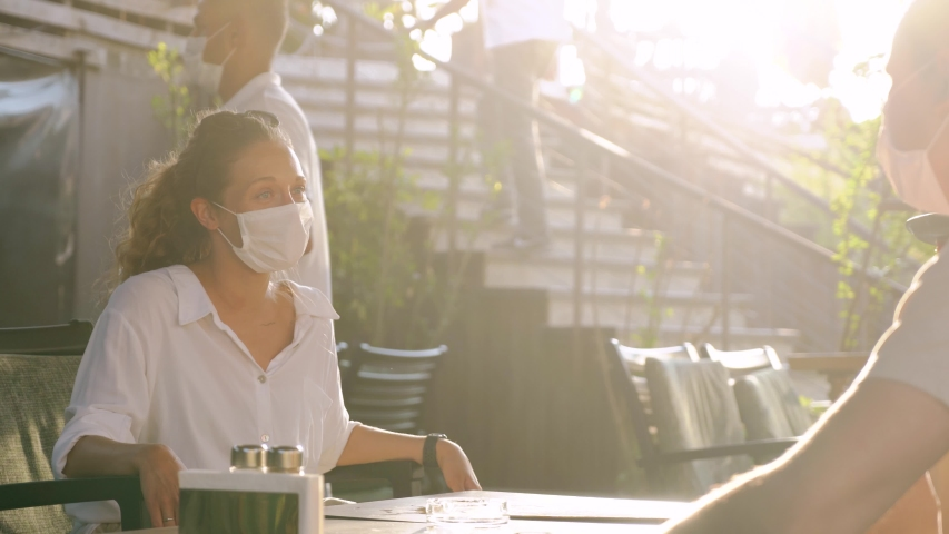 Waitress with protective medical mask and gloves serving guest with cocktails in outdoor restaurant. Opens new concept after quarantine, 4K | Shutterstock HD Video #1055634551