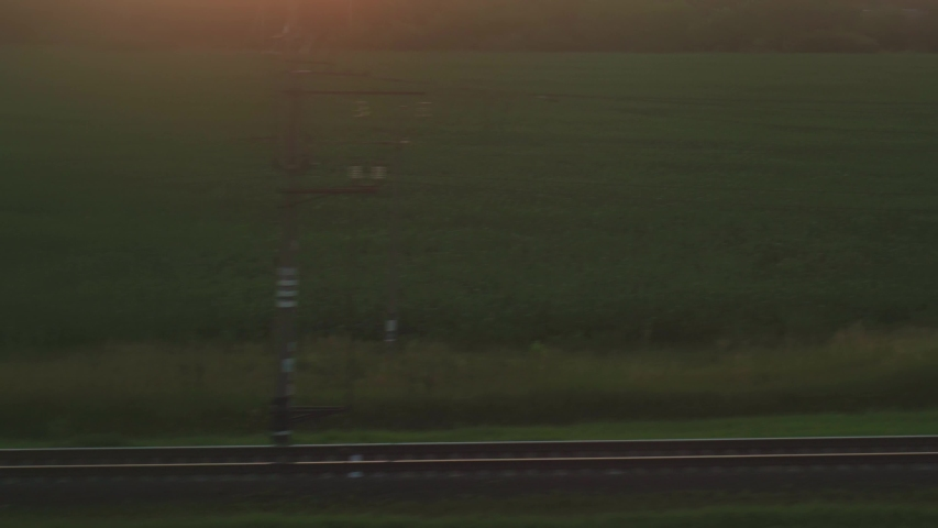Transport, travel, road, railway, landscape, comnication concept - view from window of speed train with glare on glass and parallel rails on landscape of meadows and forest before sunset in summer | Shutterstock HD Video #1055650031