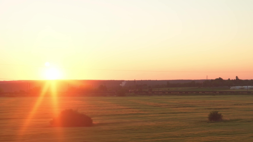 Transport, travel, road, railway, landscape, comnication concept - view from window of speed train with glare on glass and parallel rails on landscape of meadows and forest before sunset in summer | Shutterstock HD Video #1055650034