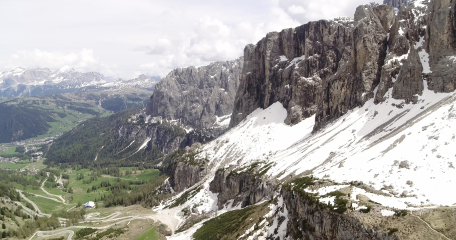 Aerial over Sella, snow covering mountain and green meadows in the valley below   Shutterstock HD Video #1055651951