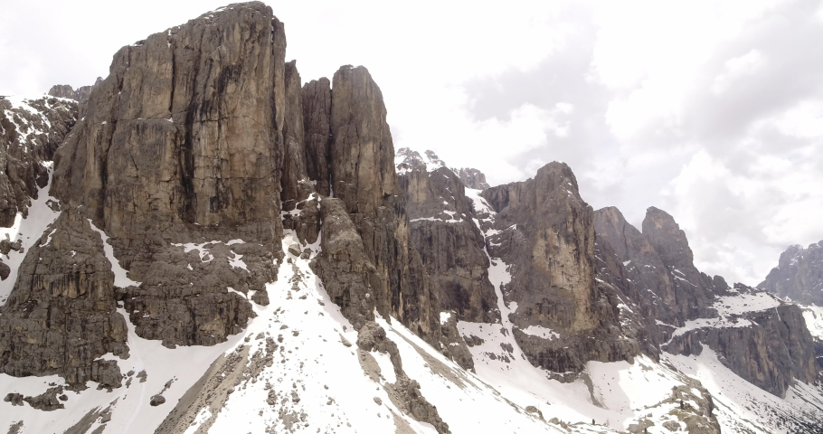Sella in the Dolomites. Aerial in the Alps. Snow on the mountains in spring 4K   Shutterstock HD Video #1055651954