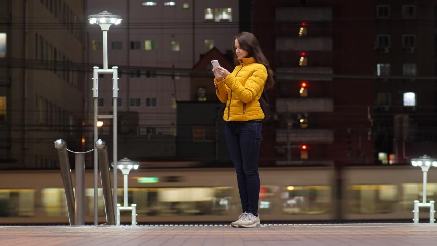 Woman stand using phone, full length shot. Dark city buildings, metro train run on background. Tourist lady somewhere at Osaka city. Night time | Shutterstock HD Video #1055652326