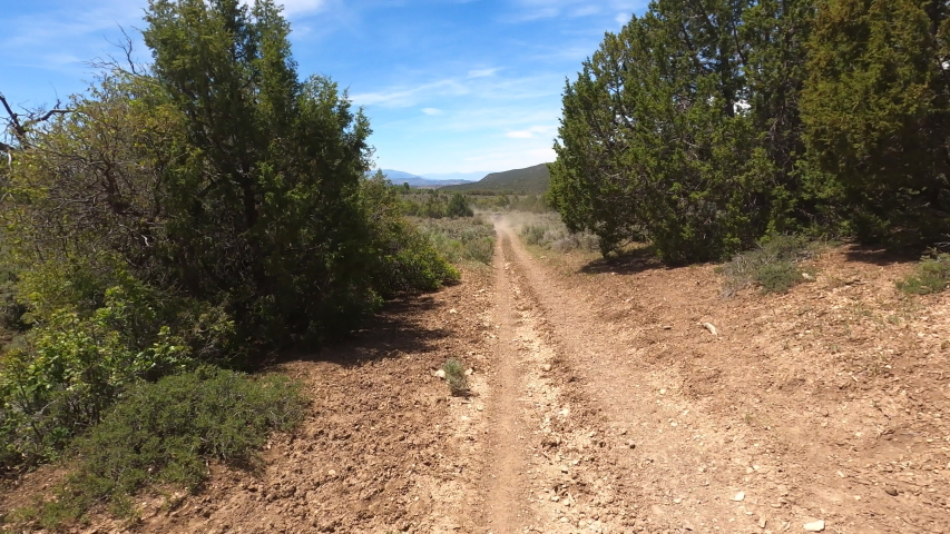 Outdoor off road recreation dusty mountain trail OHV 4K POV. Off road trail riding in 4x4 all terrain vehicle for sport and recreation. Dry arid landscape. Grass lands, rocky terrain and sand dunes. | Shutterstock HD Video #1055655902