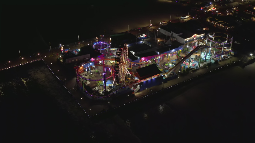 AERIAL: Breathtaking view on Santa Monica Pier at night with Ferris Wheel and colorful lights,  | Shutterstock HD Video #1055656151