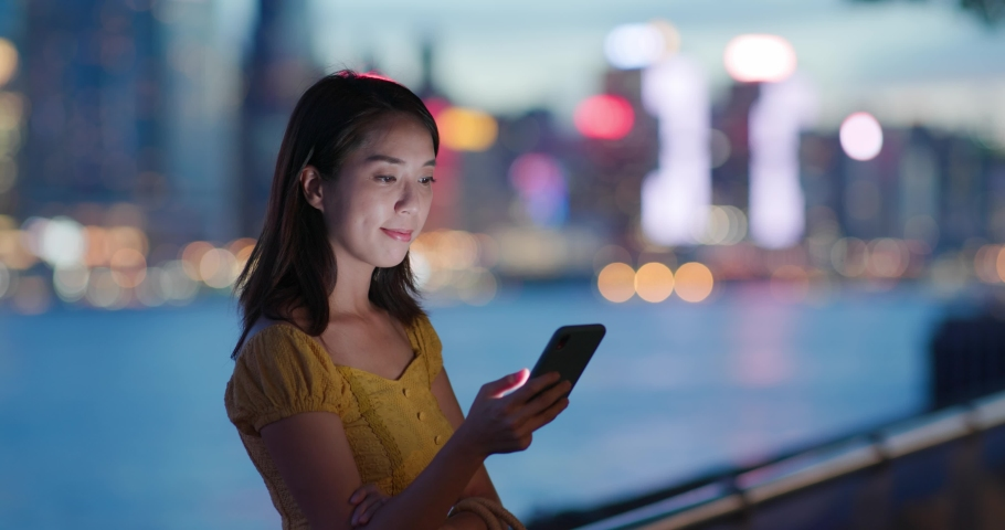 Woman use of mobile phone at night in city | Shutterstock HD Video #1055657732