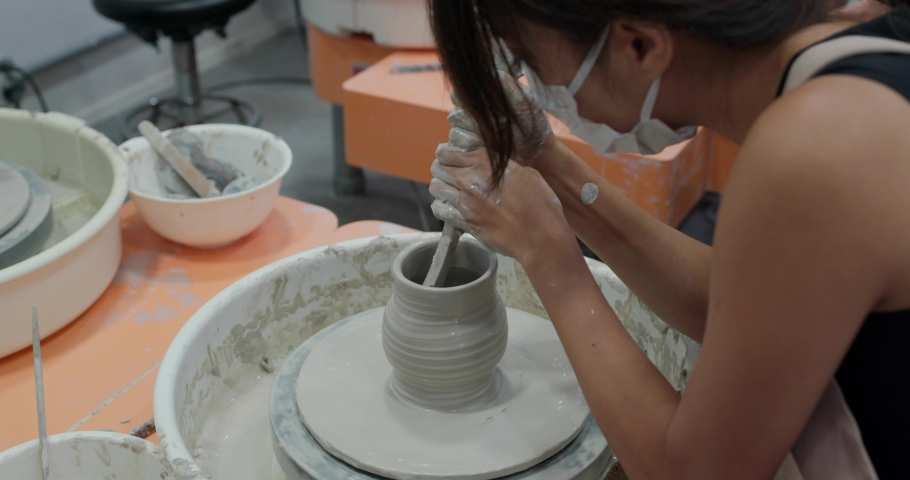 Woman make pottery wheel, shaping a clay pot | Shutterstock HD Video #1055657741