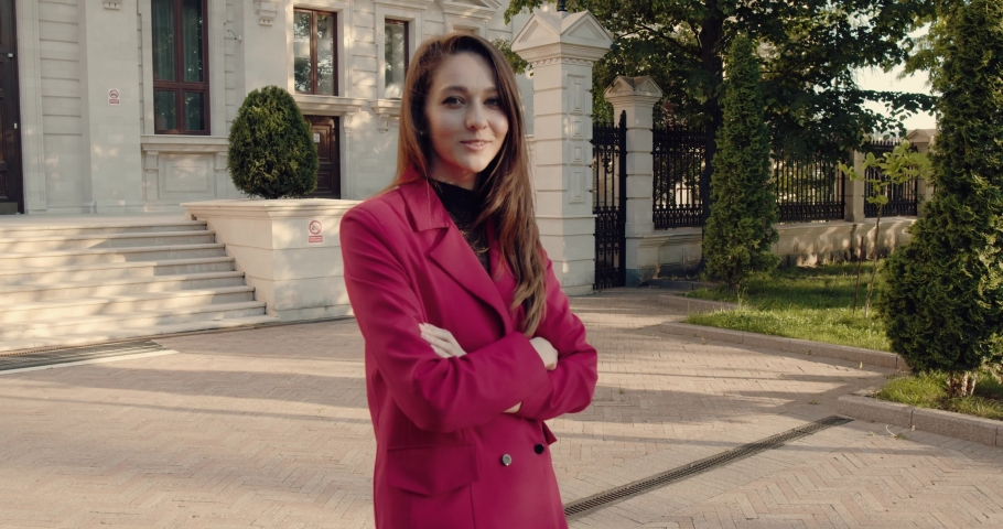A pretty woman in front of a business center, dressed in red, smiling and in a good mood. The young lady looks directly at the camera. | Shutterstock HD Video #1055660636