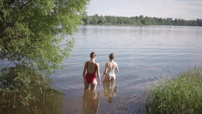 Two female friends swimming in river during sunny day   Shutterstock HD Video #1055664884