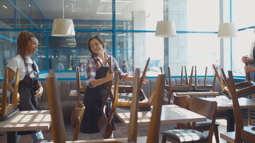 Cafe waiters smile and chat raising chairs to arrange in preparation for closing coffee shop. Team of restaurant staff in aprons cleaning cafe after closing in evening | Shutterstock HD Video #1055679269