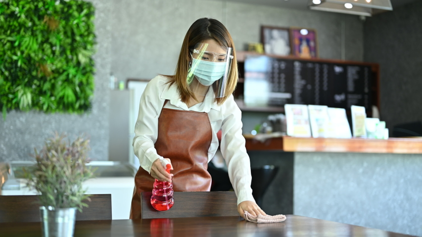 New normal startup small business Portrait of Asian woman barista wearing protection mask and face shield cleaning table in coffee shop while opening in social distancing Royalty-Free Stock Footage #1055683337