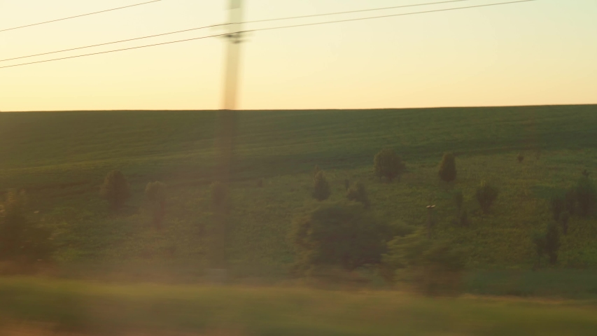 Transport, travel, road, railway, landscape, comnication concept - view from window of speed train with glare on glass to landscape of beautiful nature of meadows and forest before sunset in summer | Shutterstock HD Video #1055686697