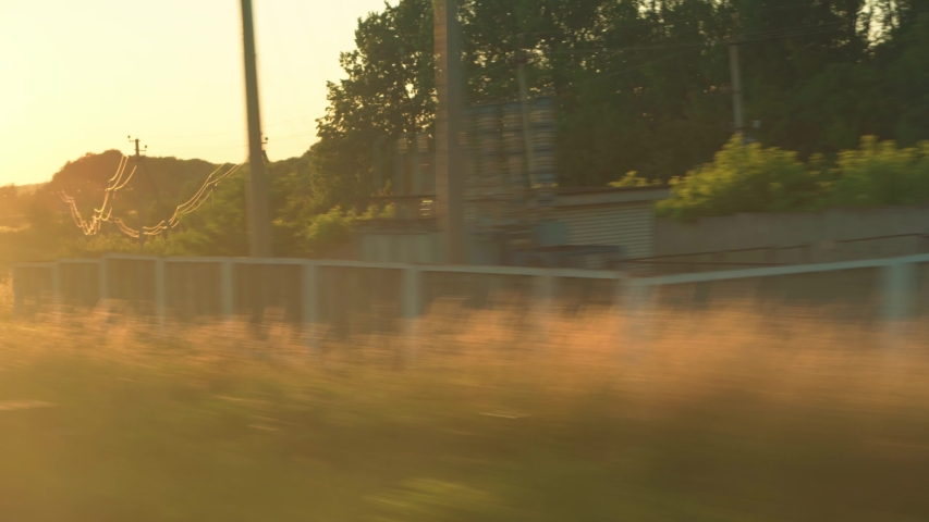 Transport, travel, road, railway, landscape, comnication concept - view from window of speed train with glare on glass and parallel rails on landscape of meadows and forest before sunset in summer | Shutterstock HD Video #1055686700