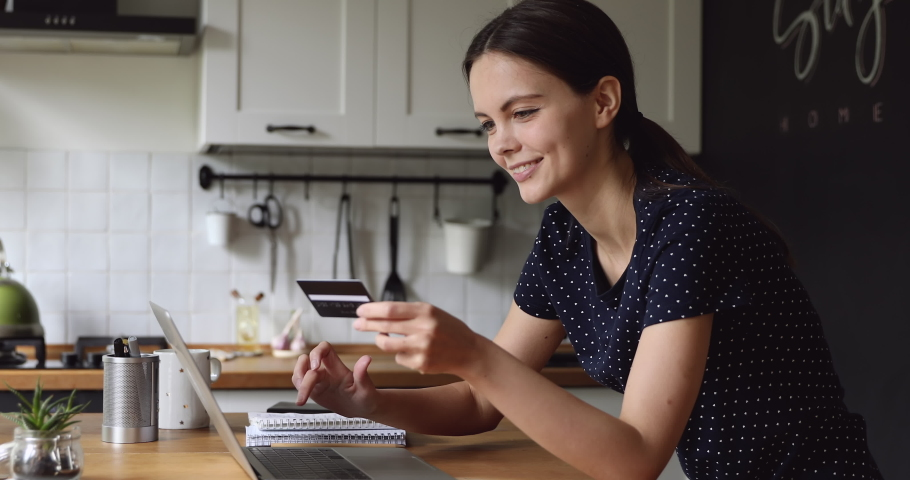 E-bank easy quick money transfer, convenient usage, on-line buying, secure payment of internet services concept. Young woman standing in kitchen holding credit card using laptop enjoy online shopping Royalty-Free Stock Footage #1055702621