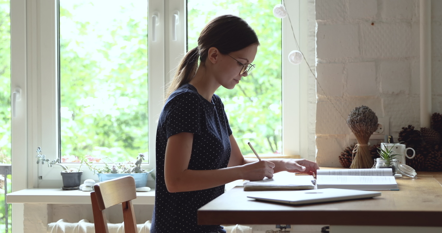 Translator translates text working sit at table at home. Student wear glasses hold pencil noting makes overview writing on copybook smile enjoy self-education process. Study gain new knowledge concept Royalty-Free Stock Footage #1055702744