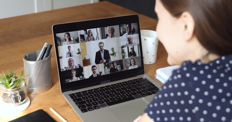 Different age ethnicity people engaged in video call communication, laptop screen view over woman shoulder sit at desk looks at pc involved in conversation. Internet space virtual visual talk concept | Shutterstock HD Video #1055702777