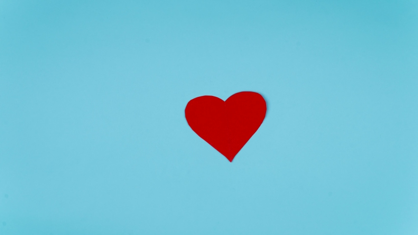 Stop motion of red paper in the shape of heart symbol while moving on table with loopable seamless background. Shot in 4k resolution | Shutterstock HD Video #1055708651