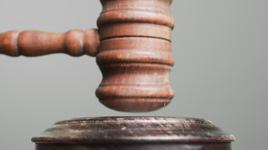 Gavel being struck to decide an auction or guilty verdict in court. Grey background. Slow motion. Royalty-Free Stock Footage #1055715704