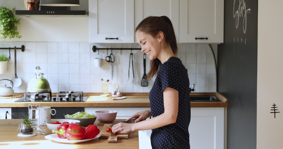Smiling slim young woman holds knife cuts cherry tomatoes preparing salad cooking vegetable dish moves to music listens song dancing in kitchen feels carefree. Healthy eating, pleasant routine concept