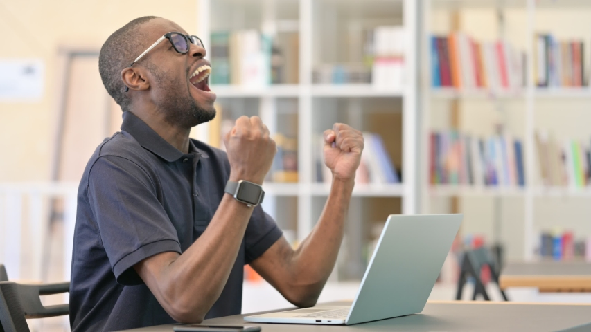 African Man Celebrating Success on Laptop in Library | Shutterstock HD Video #1055728115