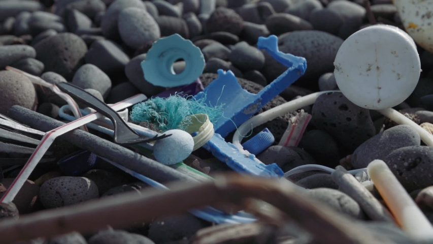 Old washed up plastic on cobblestone beach in Hawaii. Slow mo slide Royalty-Free Stock Footage #1055729789