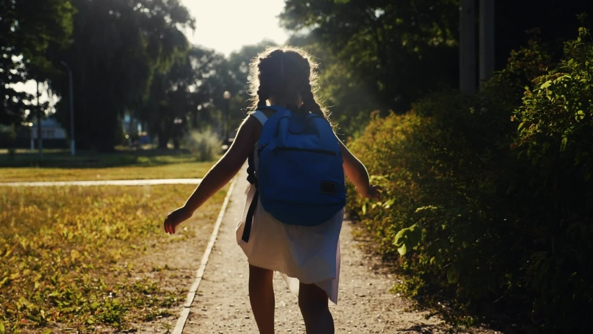 schoolgirl kid with a backpack run through the park home from school dream on a sunny day. daughter little girl with school backpack running home after school. concept education run children learning Royalty-Free Stock Footage #1055779325