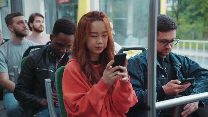 Chinese attractive girl with red hair texting message on smartphone driving inside tram public transport. Commuting. Travel. Urban. Technology. | Shutterstock HD Video #1055781794